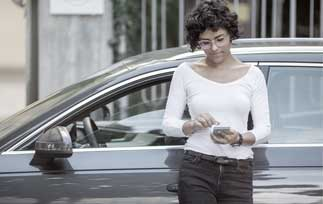 Lady waiting by car with her phone in her hand