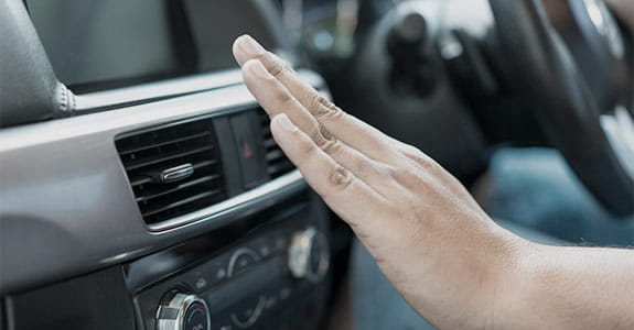 Someones hand in front of a car vent