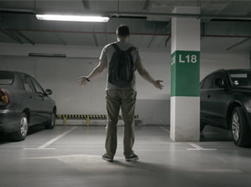 A man in a parking garage looking for his car