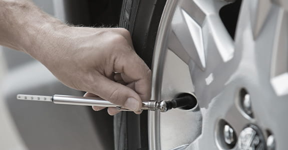 Someone checking air pressure on a car tire