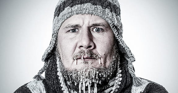 Bearded man in stocking cap with icicles on face