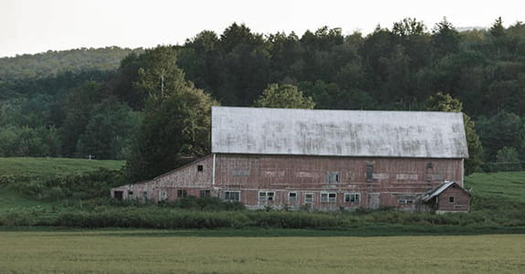 Faded red barn in a field
