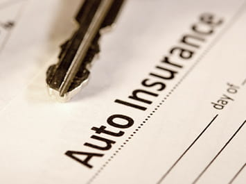 Tip of a car key on an auto insurance form