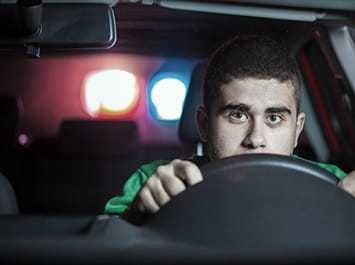 Man behind the wheel of a car with red and blue cop car lights flashing through the back window