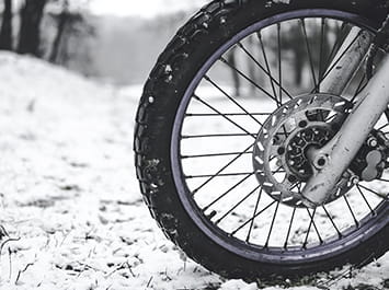 Motorcycle wheel on the snow covered ground