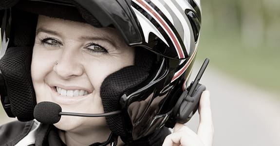 A woman wearing a bluetooth motorcycle helmet