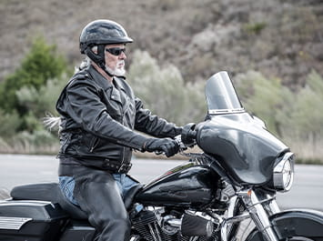 Guy sitting on a motorcycle with a black helmet on