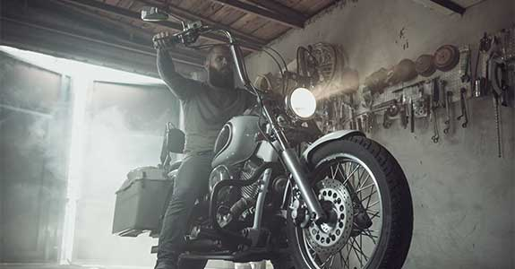 Man on a motorcycle while in a garage