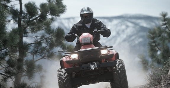 Someone riding a red ATV on a trail