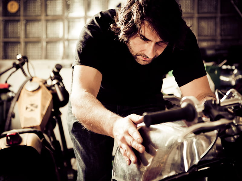 man working on motorcycle tank