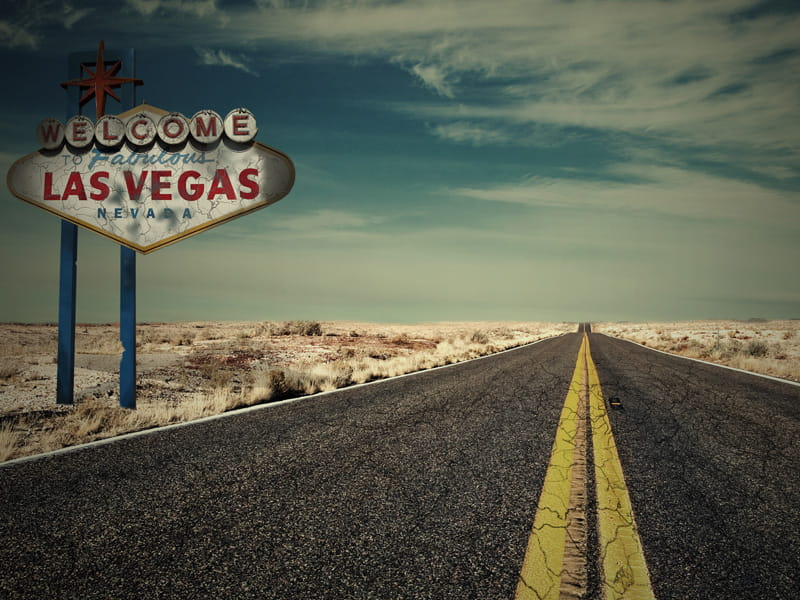 Vegas sign next to a road