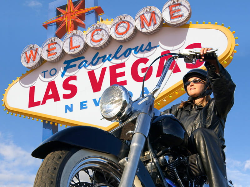 woman on motorcycle in front of las vegas sign